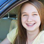 תלמידת נהיגה מאושרת יושבת באוטו ומחייכת למצלמה