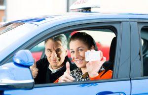 תלמידה מאושרת קיבלה רישיון נהיגה ומצטלמת עם המורה נהיגה שלה